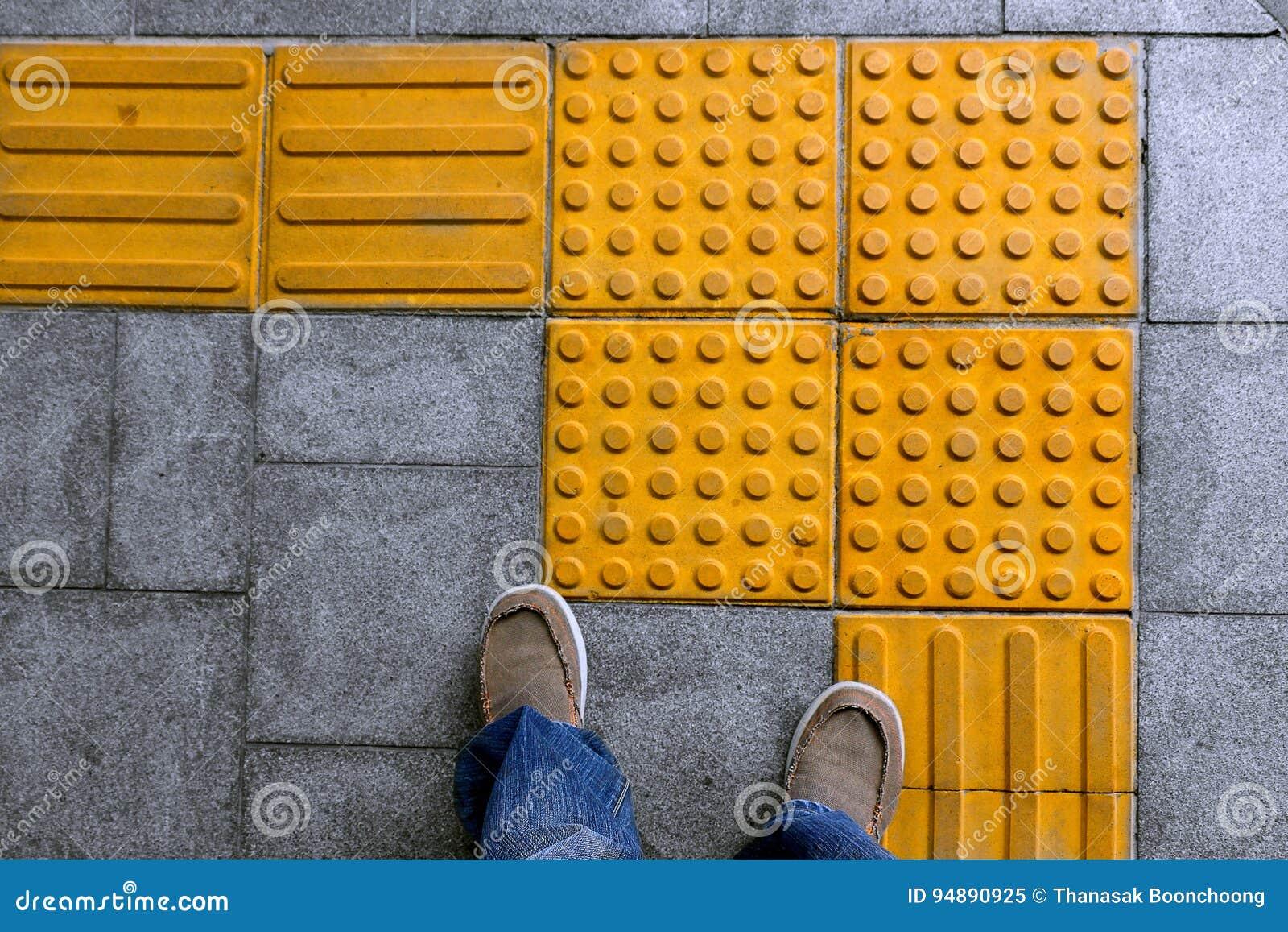 Scarpe sulla pavimentazione tattile del blocco per l handicap cieco