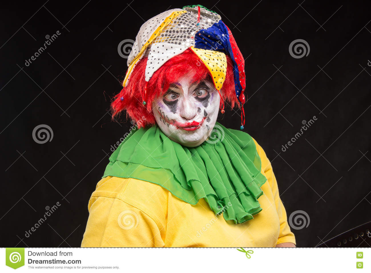 scary clown joker with a smile and red hair on a black backgroun