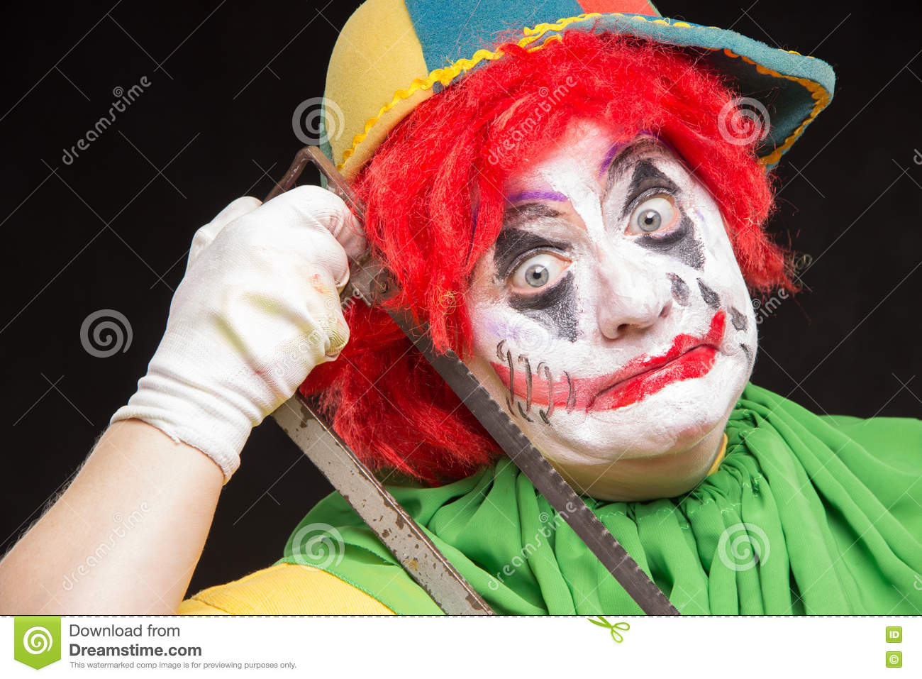 scary clown joker with a smile and red hair with a saw on a blac