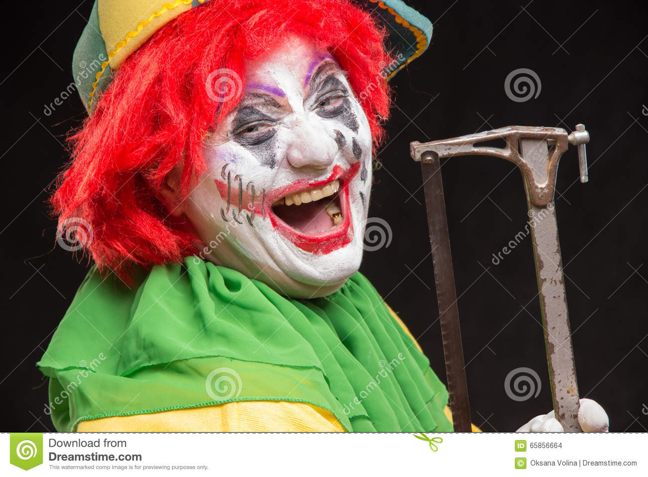 Scary Evil Clown With An Ugly Smile And Saw On A Black Background Stock Photo - Image -2755
