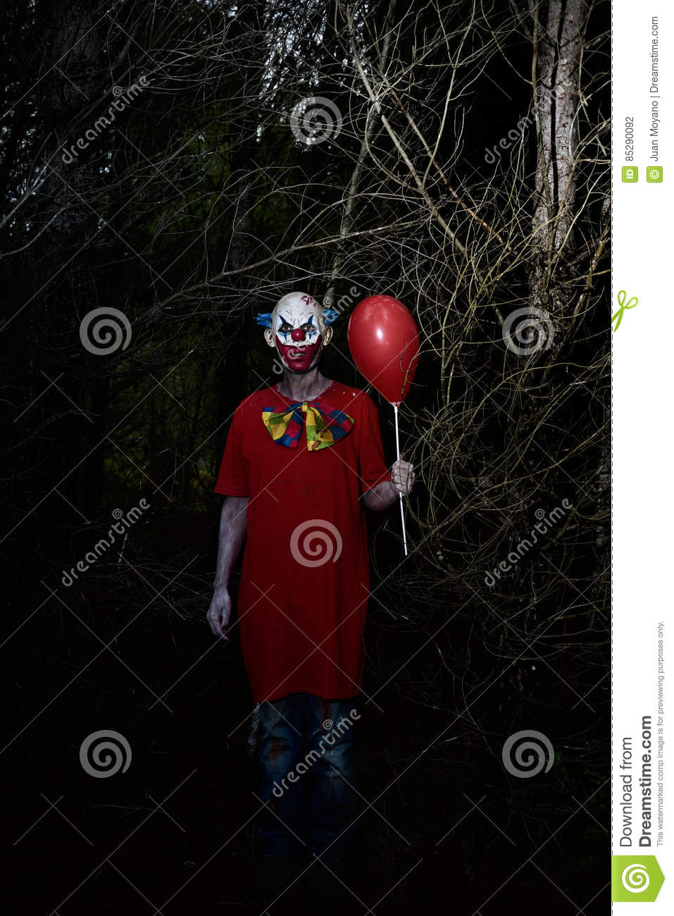 Scary evil clown in the woods at night