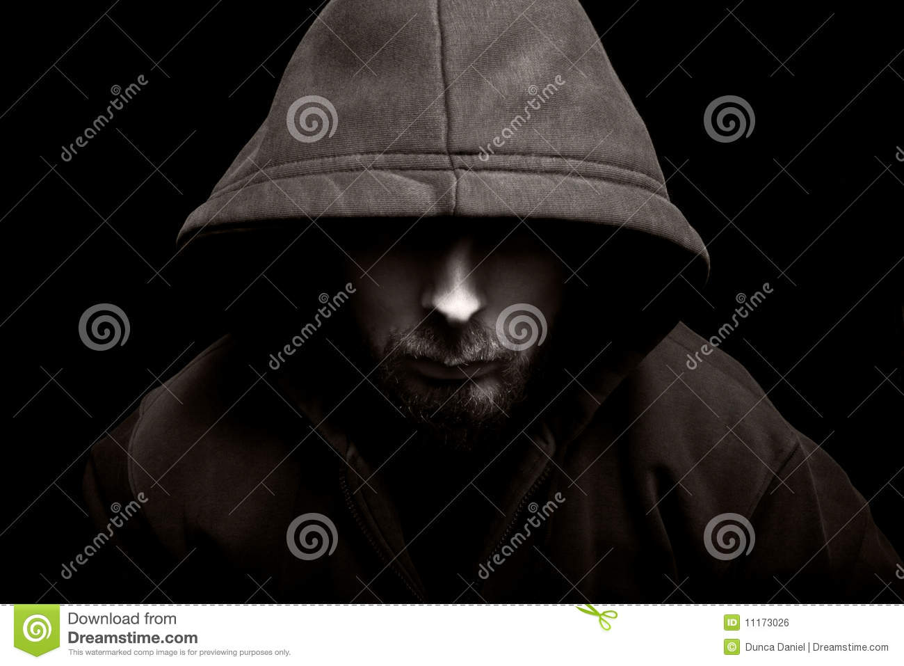 Scary evil man with hood in the dark