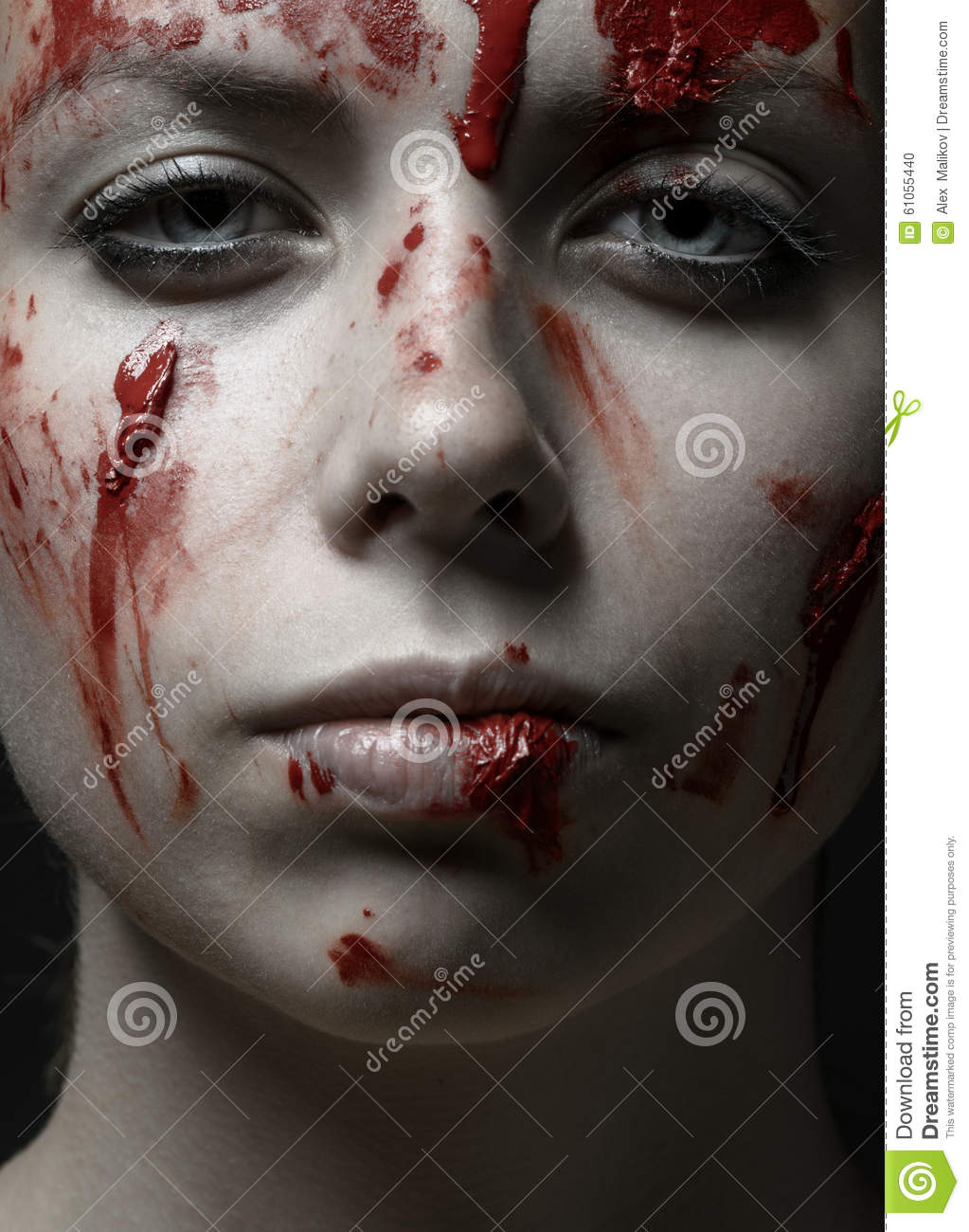 Scary Girl and Halloween theme: portrait of a crazy girl with a bloody face in the studio