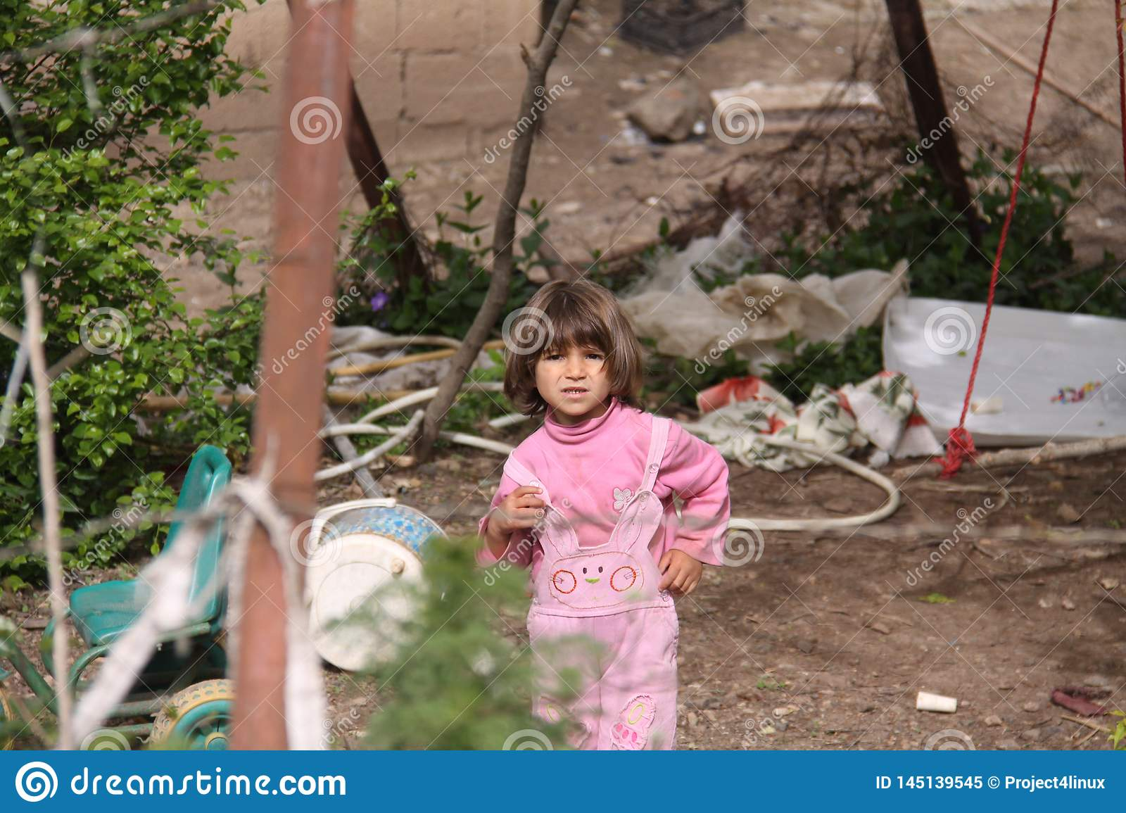 A scary little girl outside the city, A swing, different equipment and plants are visible in background, Iran, Gilan