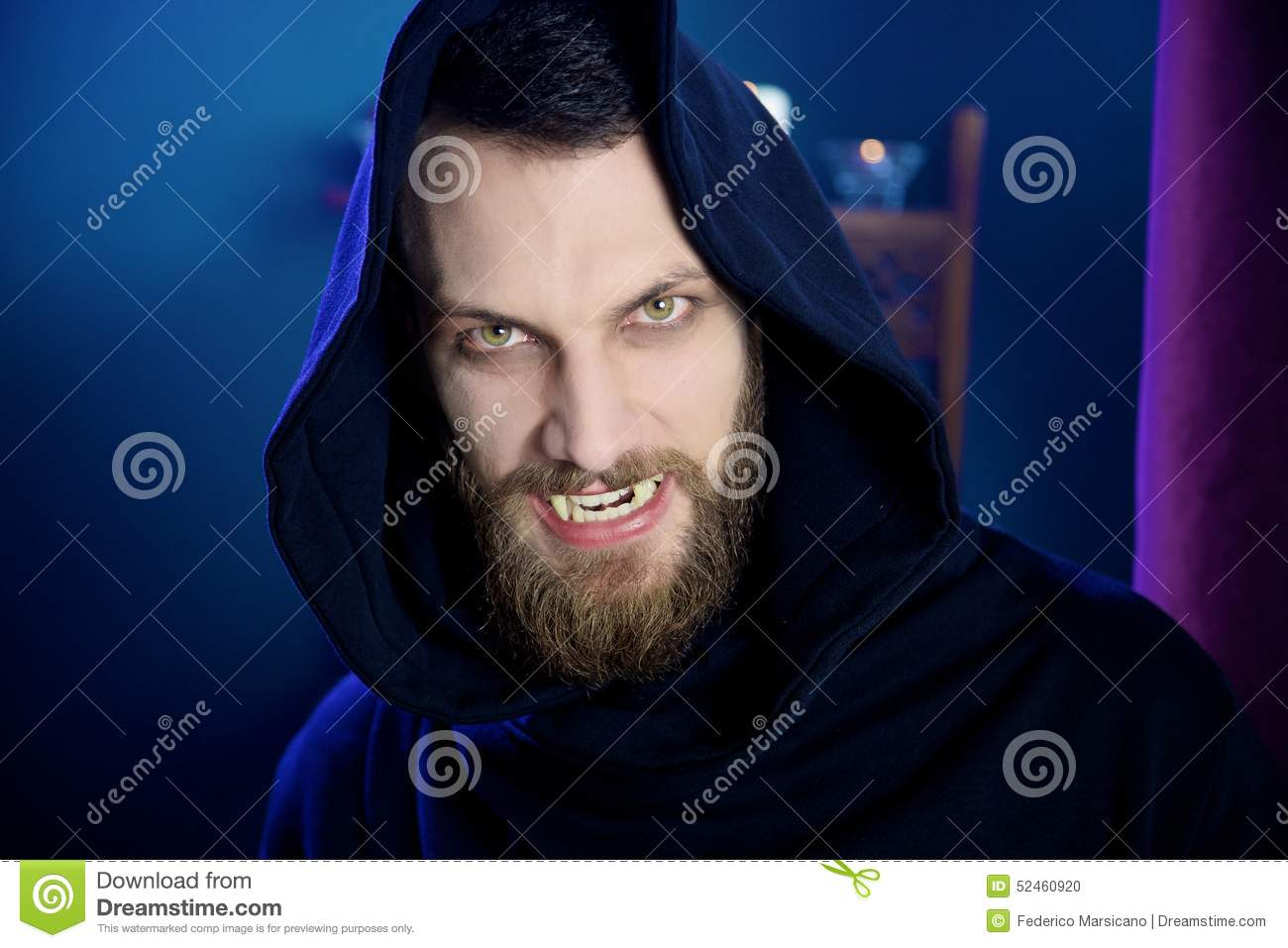 Scary male vampire looking camera with fangs
