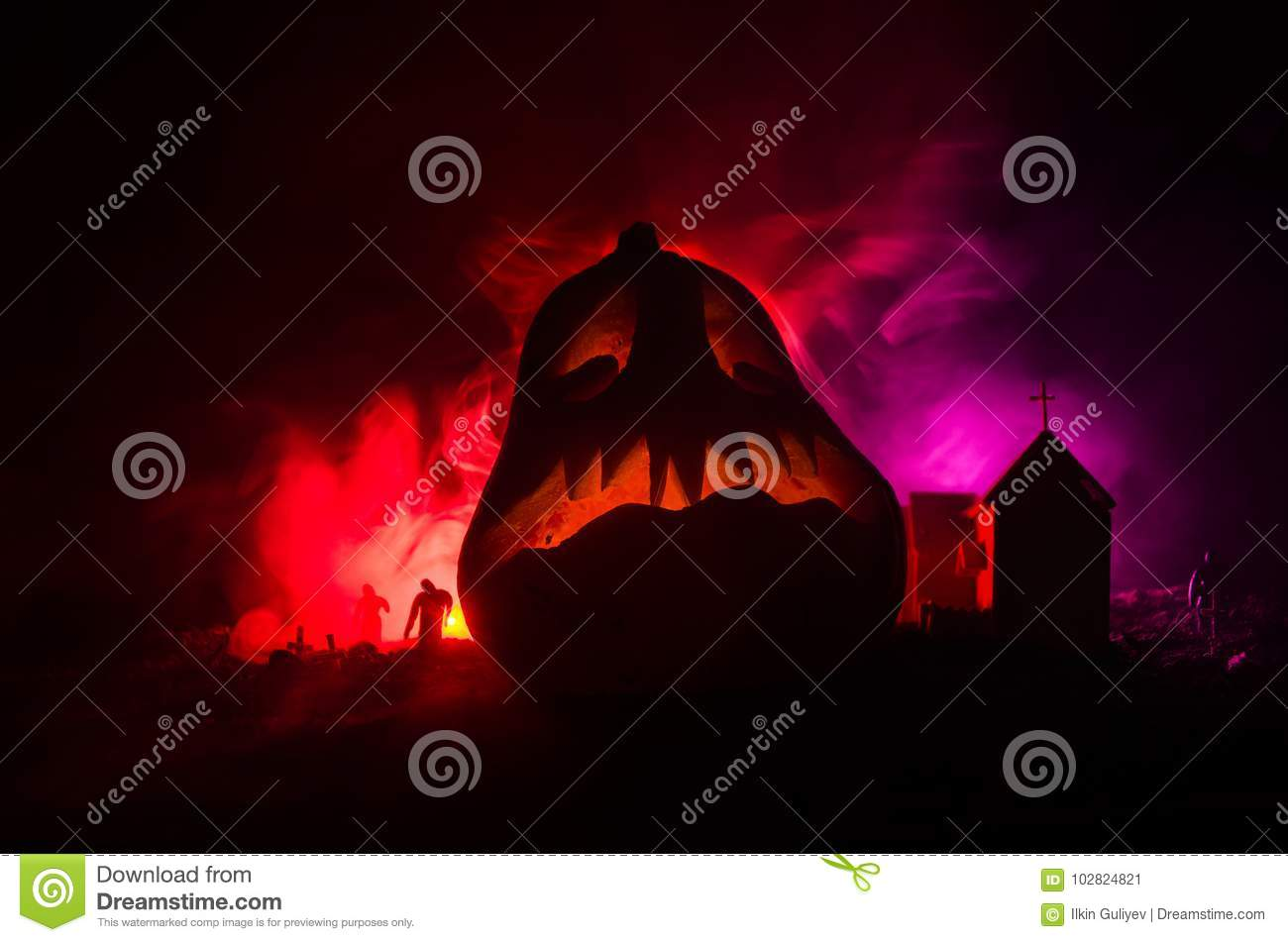 Scary view of Halloween pumpkin with zombies at cemetery bear the church and spooky cloudy sky with fog, Horror Halloween concept.