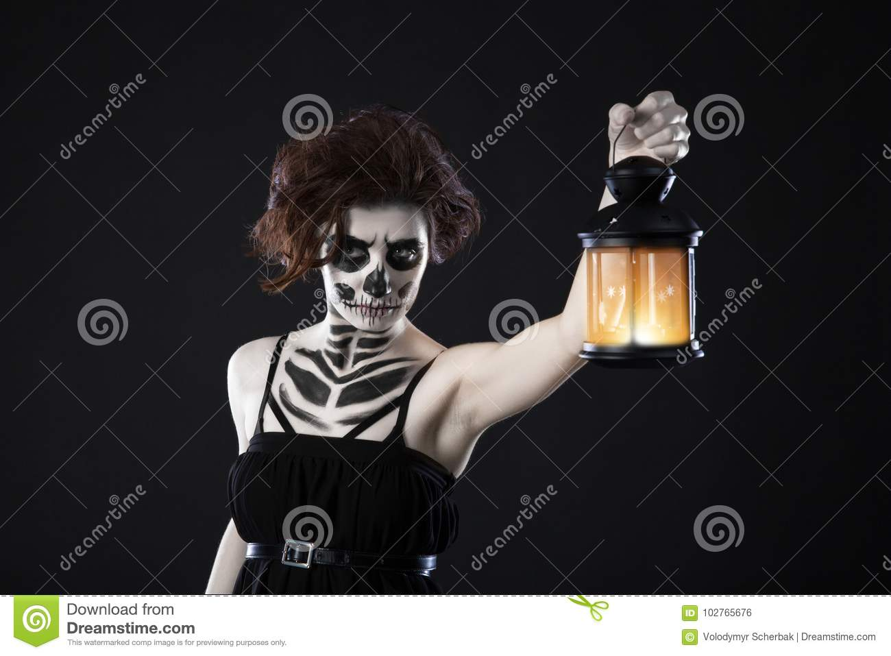 Scary woman with lantern over black background - Spooky image of a scary woman with dark eyes and appearance of a witch, in a whit