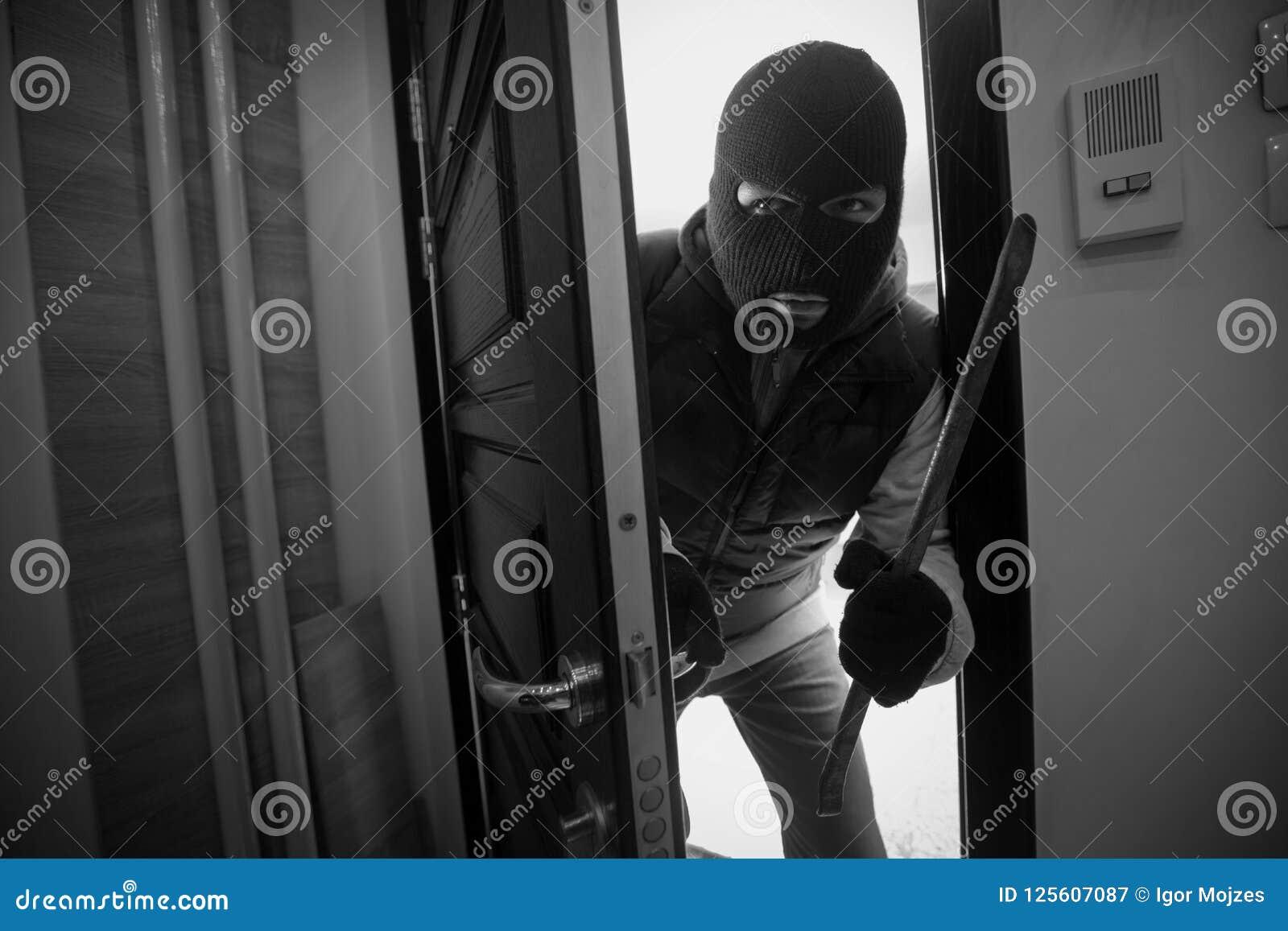 Scassinatore che irrompe una casa con il bastone a leva