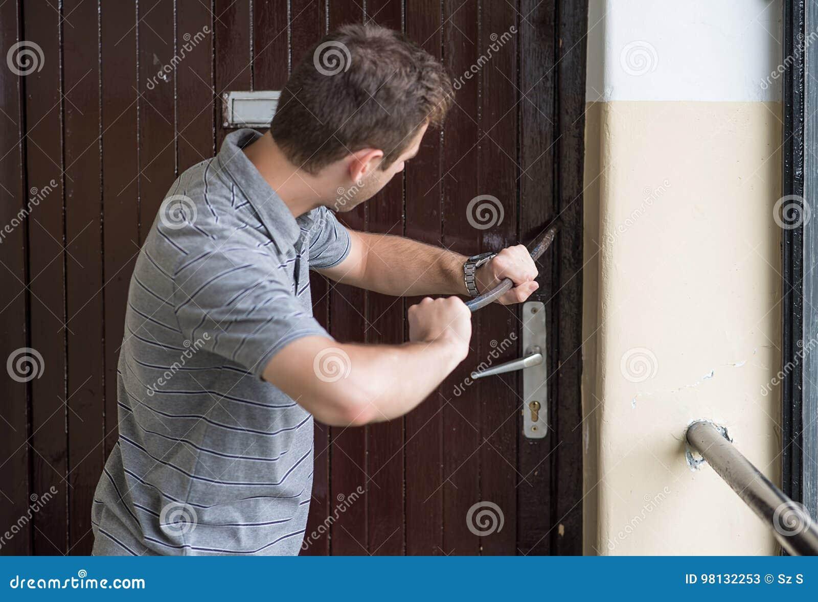 Scassinatore che prova a rompersi in una casa con un bastone a leva