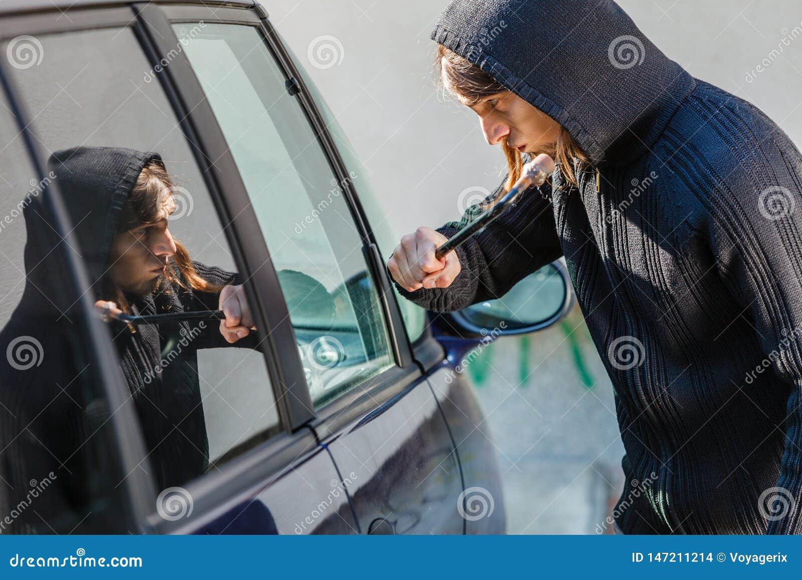 Scassinatore del ladro che si rompe fracassando la finestra di automobile