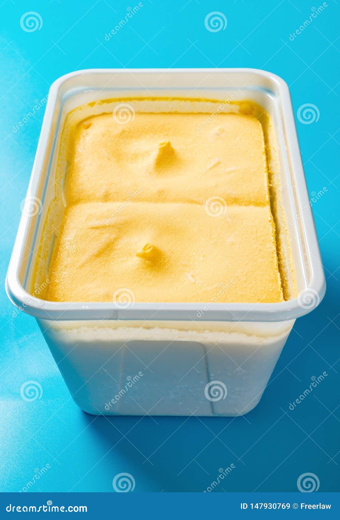 Scatola di gelato di sapore del mango sulla composizione verticale nel fondo blu