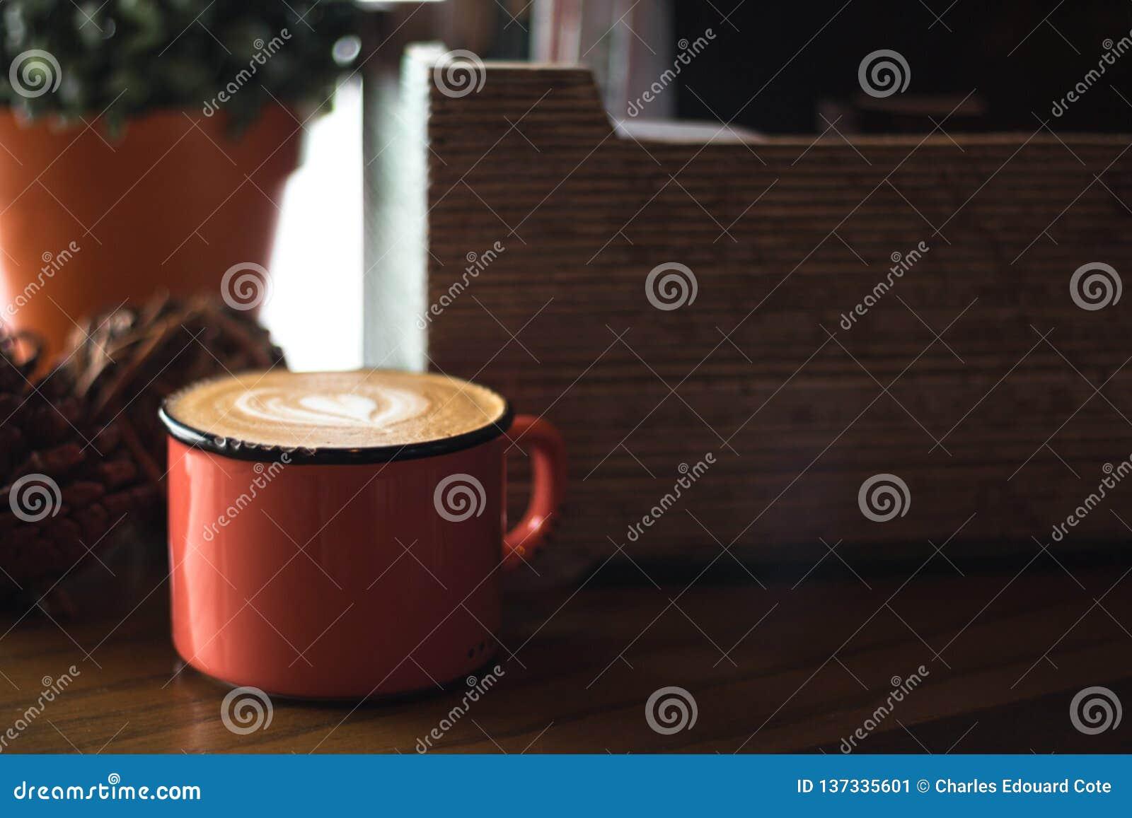 Scatola di legno e latte in una tazza rossa