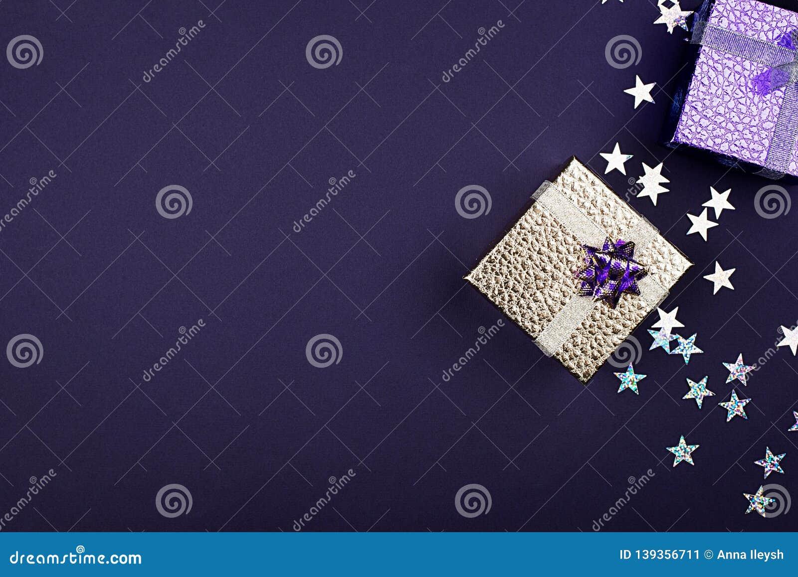 Scatola dorata festiva su un fondo porpora con le stelle delle scintille Fondo festivo per il vostro progetto orizzontale deep