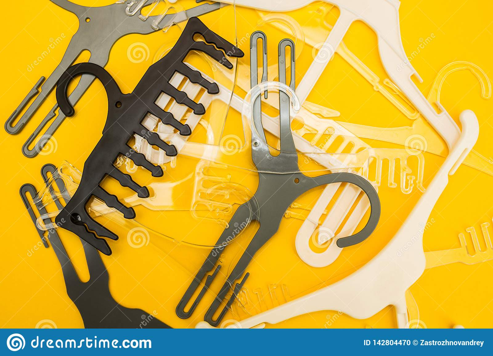 Scattered white and gray hangers on yellow background