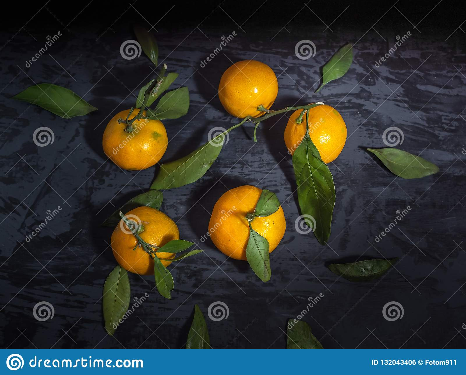 A scattering of tangerines with green leaflets on a dark background, top view