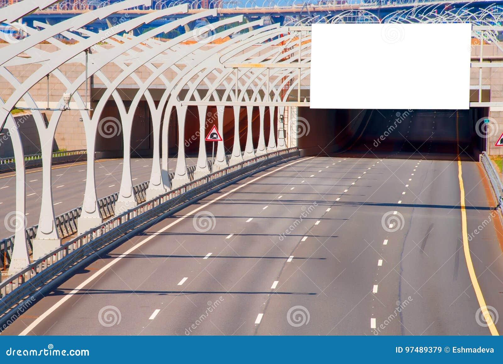Scavi una galleria sulla strada principale con il tabellone per le affissioni in bianco sopra