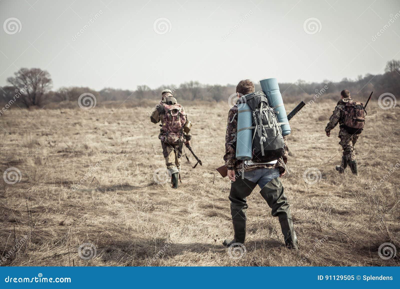 Scena di caccia con il gruppo di cacciatori con gli zainhi e le munizioni di caccia che passano attraverso il campo rurale durant