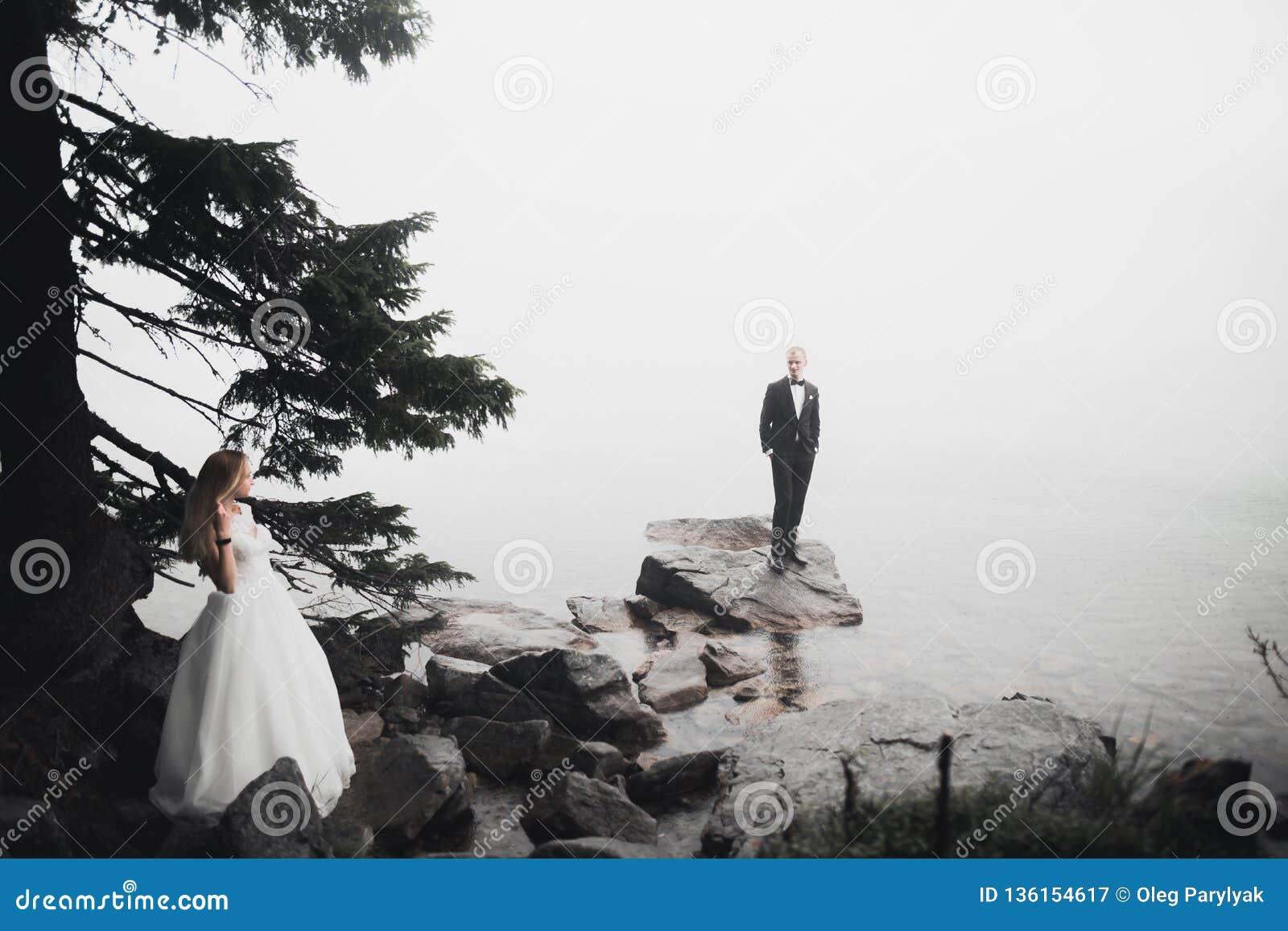 Scena felice e romantica appena di giovani coppie sposate di nozze che posano sulla bella spiaggia