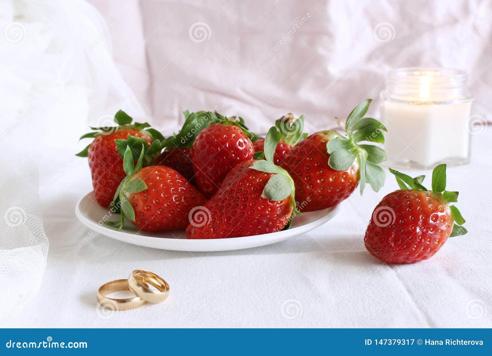 Scena luminosa di nozze, piatto della porcellana con con le fragole fresche e fedi nuziali un fondo bianco Azione disegnate femmi