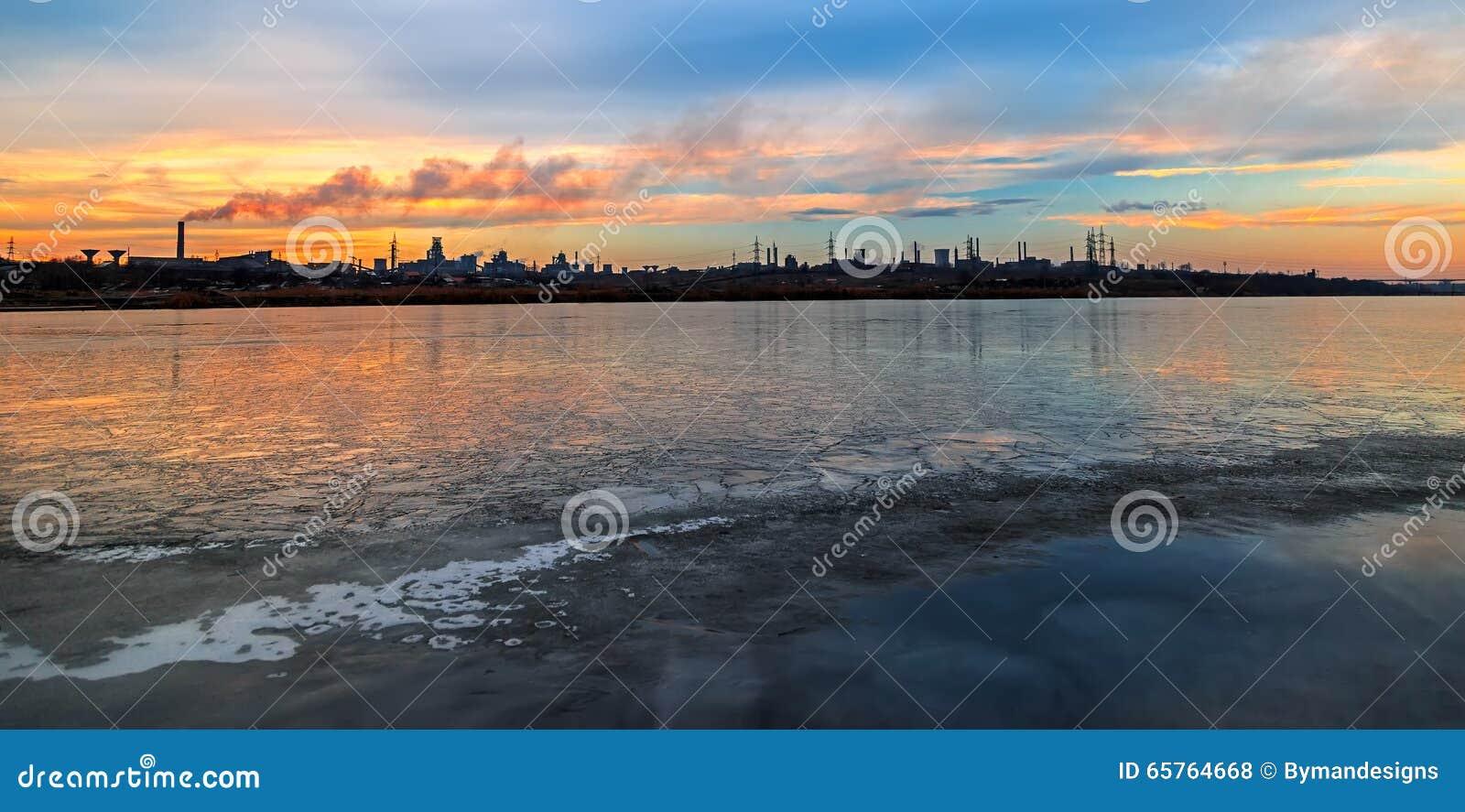Scena panoramica con il lago e la fabbrica congelati nel fondo