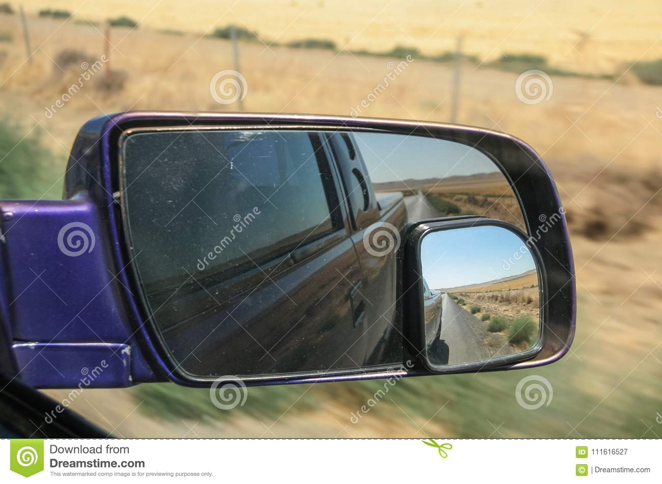 Rural scene in California, USA reflected in the rear view mirror