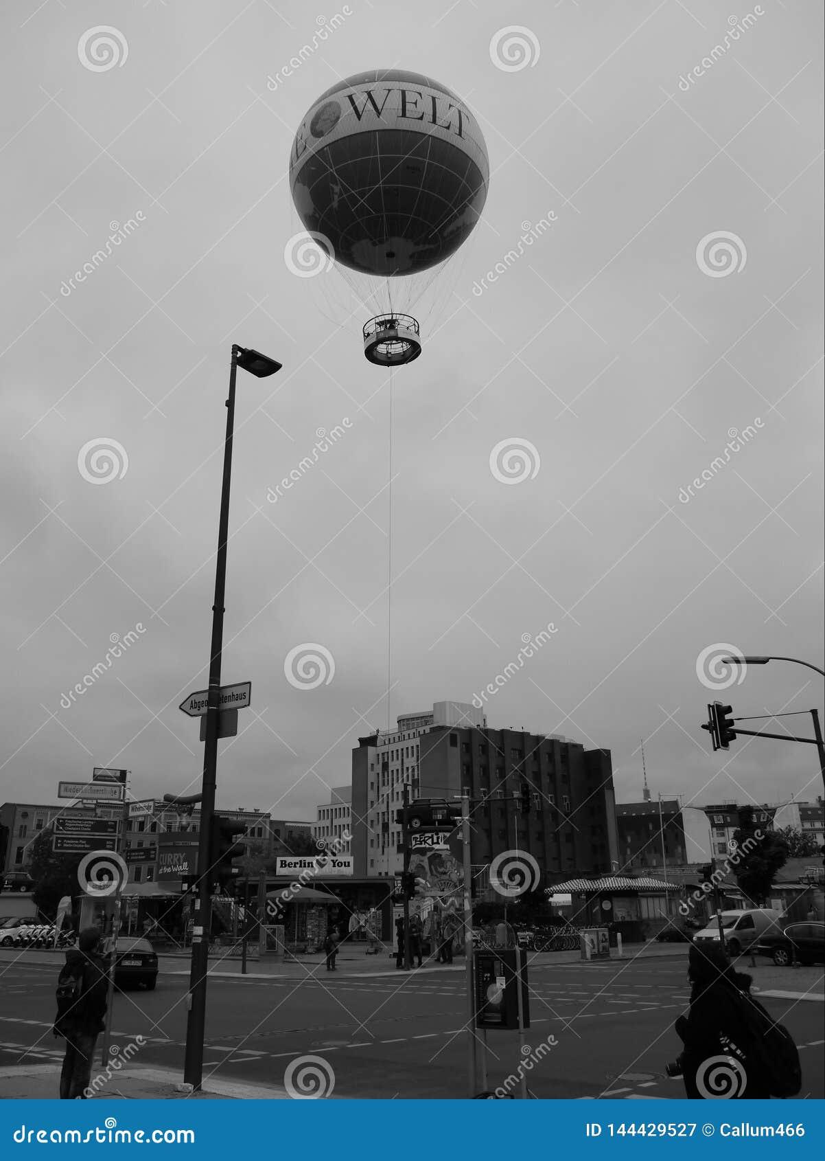 Monochrome ballon tethered to the ground above street