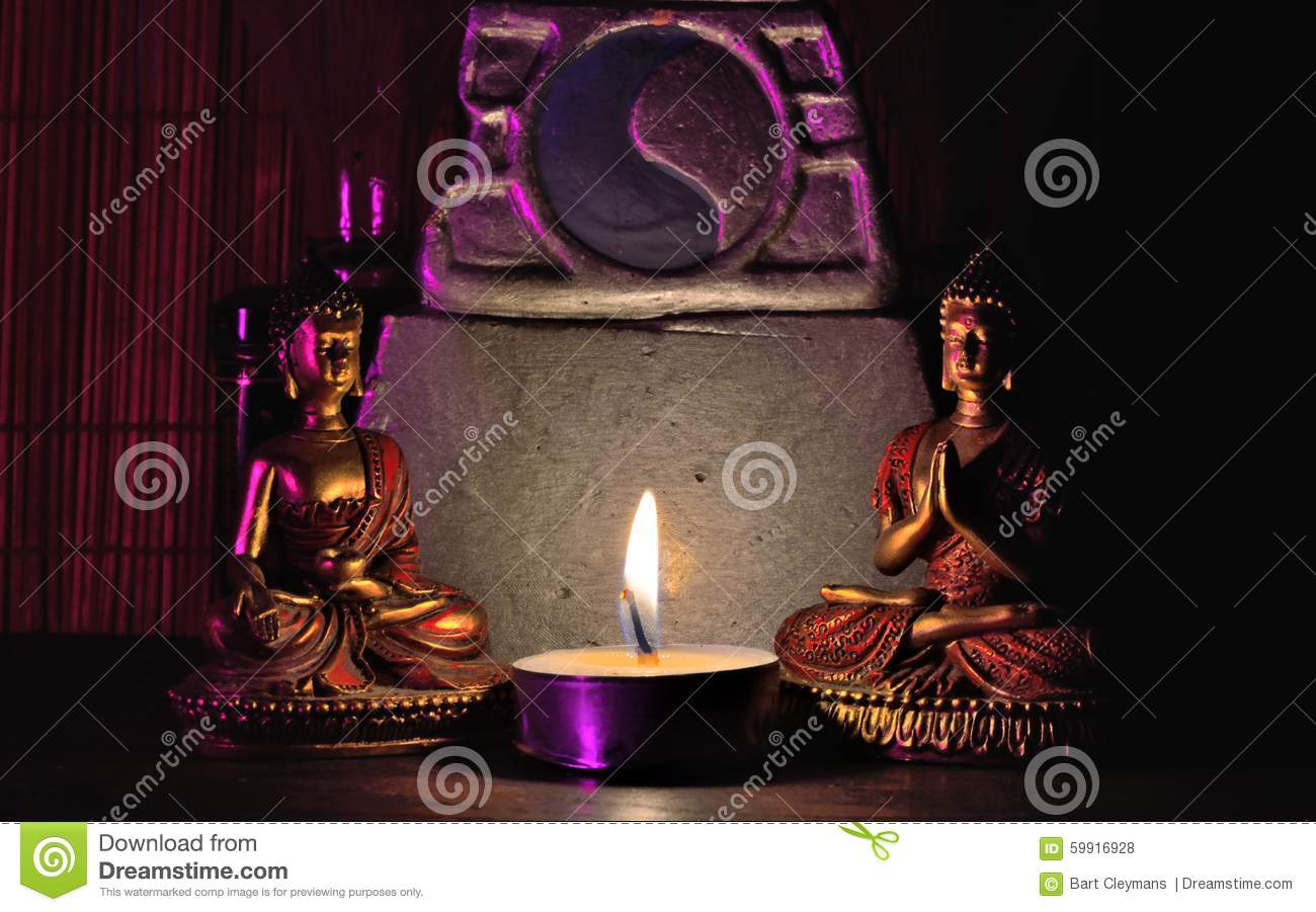 Scene: Two miniature Buddha statues, miniature altar and lighted candle,
