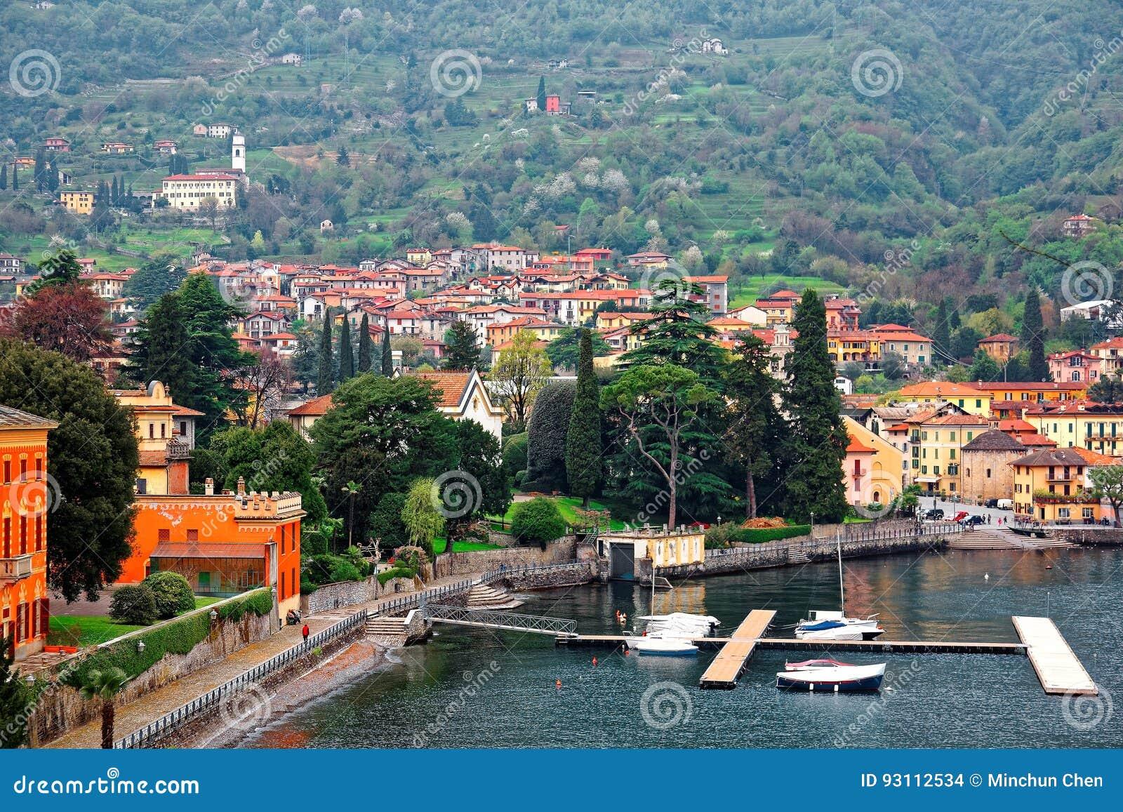 Sceneria Lenno w Lombardy Włochy, nadjeziorny miasteczko Lago Di Como parkuje dokiem z widokiem ferryboats