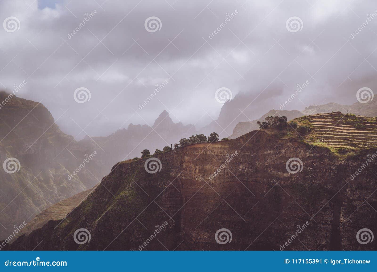 Sceneria z kształtem ogromne skały i ruch chmury zaparowywa na niebie Surrealistyczny moment przed burzą w górach dalej