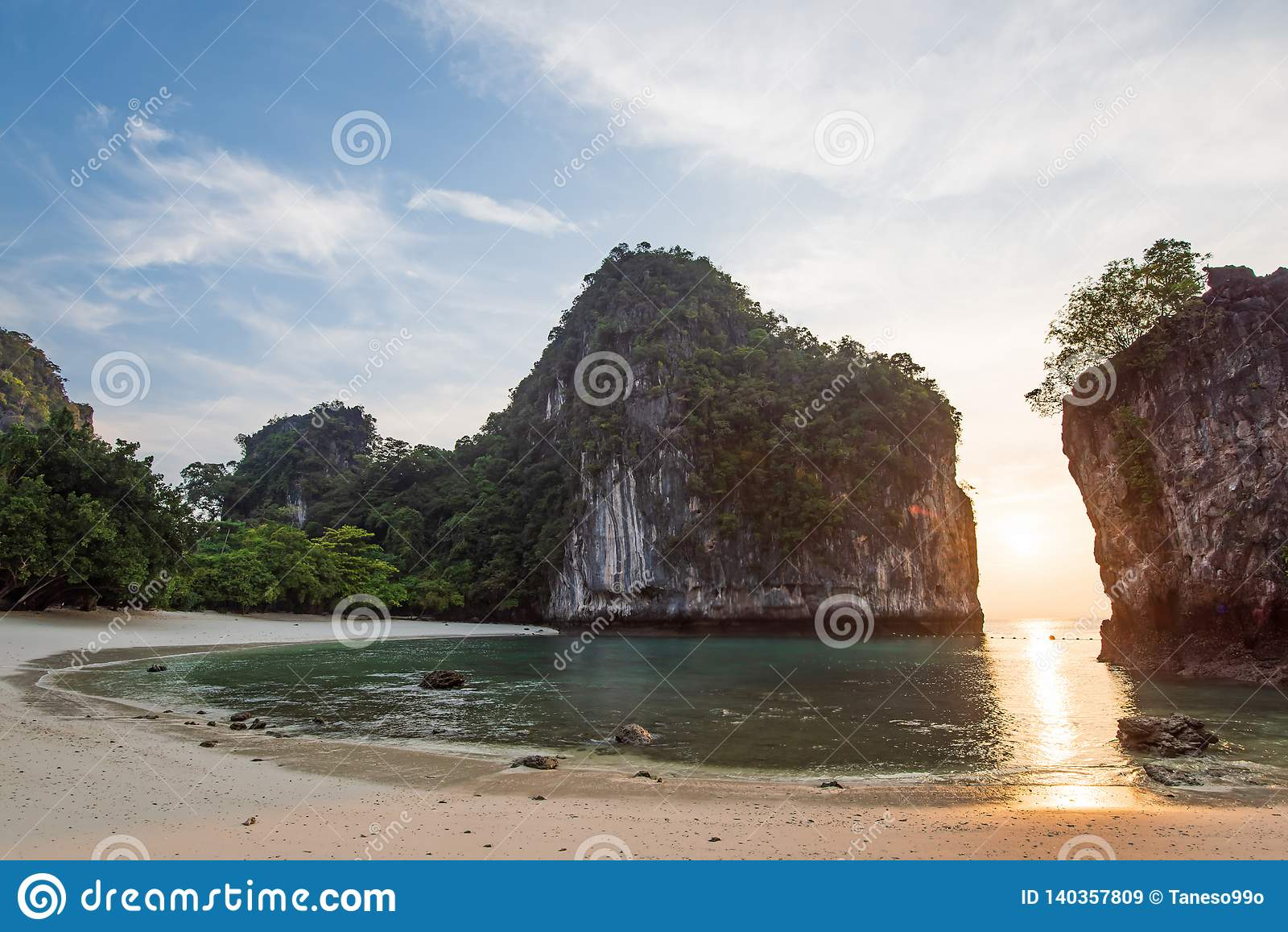 Scenic curve of tropical beach in morning light, sunrise shines through fantastic cliff on blue sea and white sand beach. Summer