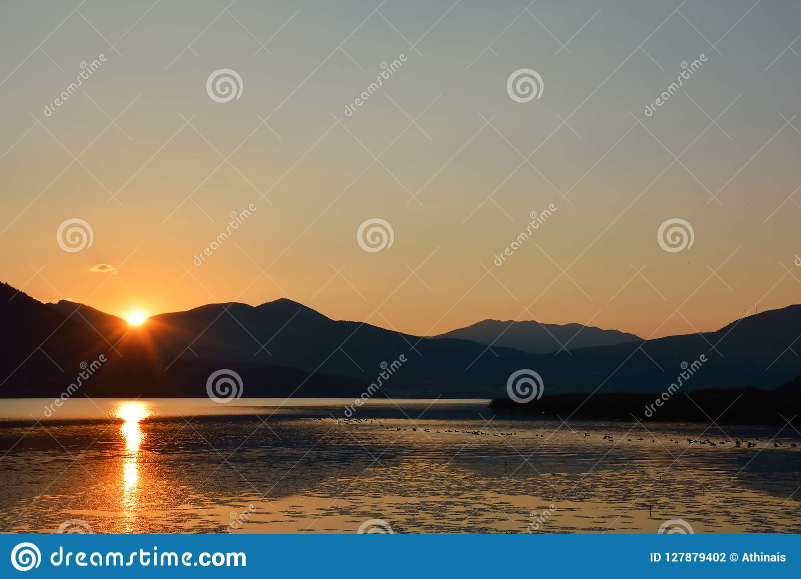 Scenic landscape of mountain ridges and sun rays reflecting in t