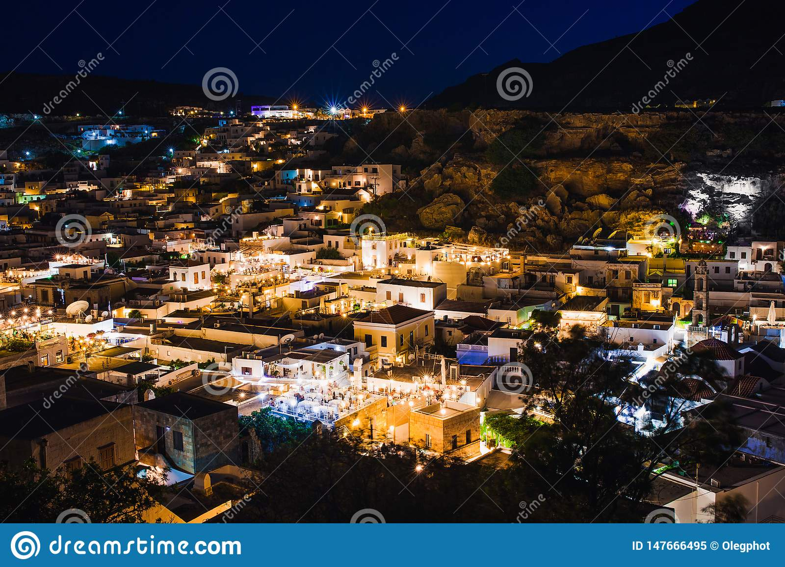 Scenic landscape photo of night Lindos town and castle on Rhodes island, Dodecanese, Greece. Panorama with bright lights,