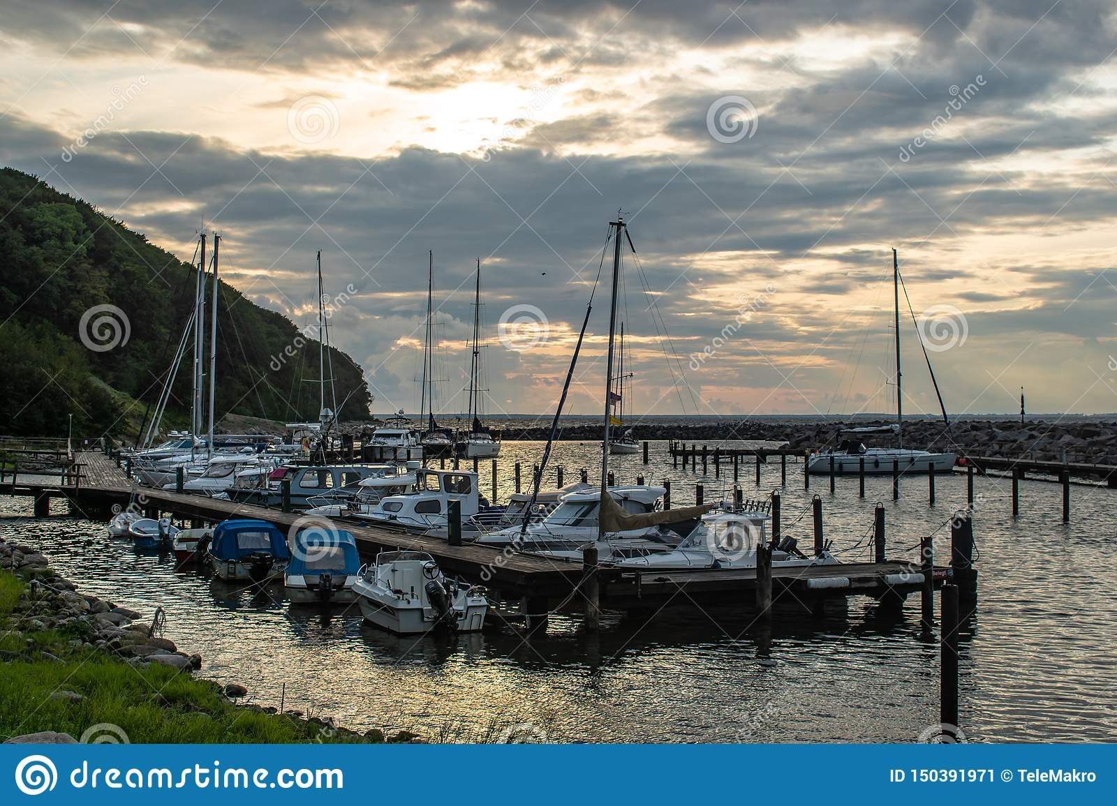 Scenic little harbour with sailing boats at sunset light