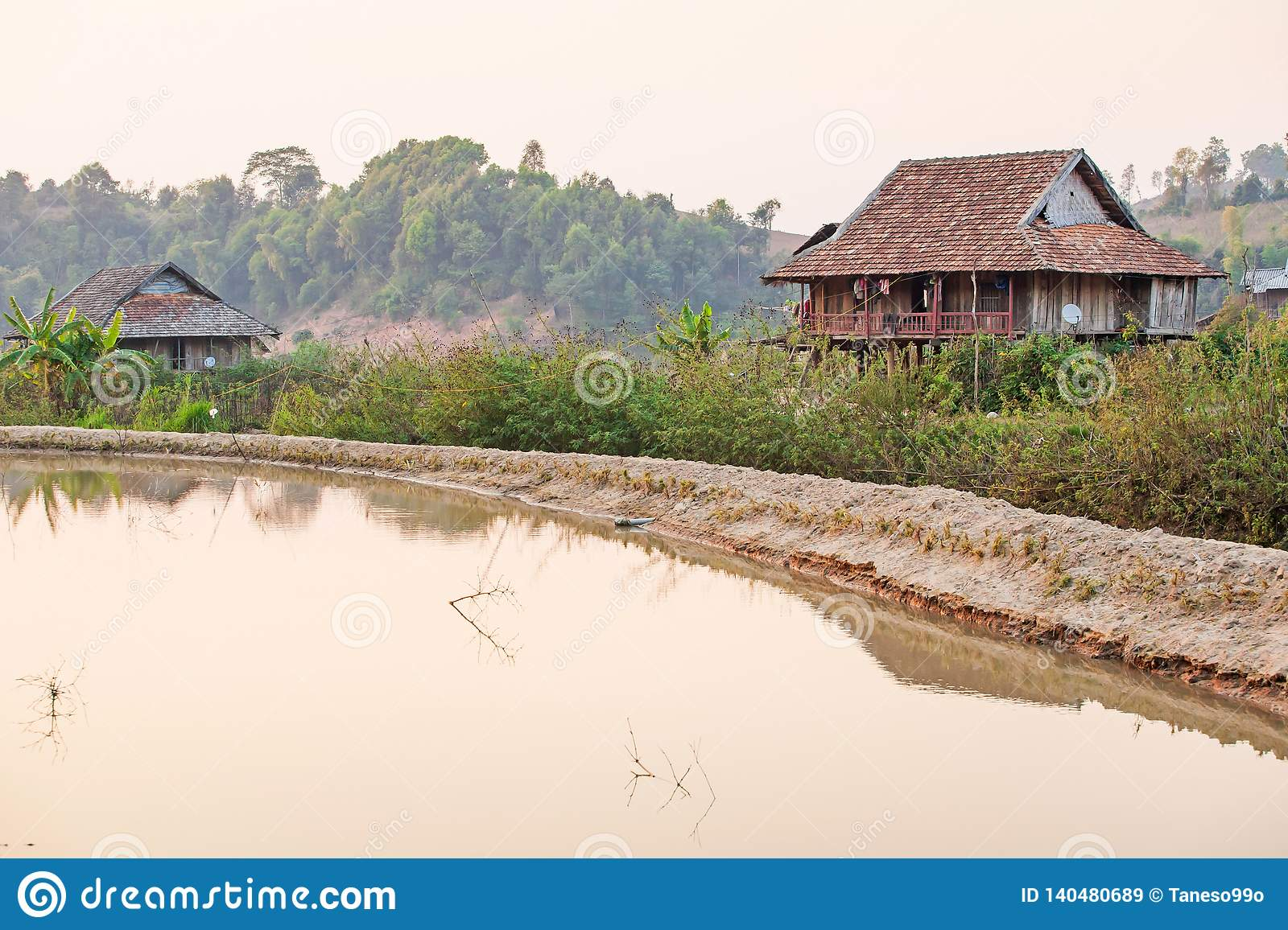 Scenic rural of vietnam at sunset, two old wooden house, brown earthenware roof, pool foreground, forest and mountains backgrounds