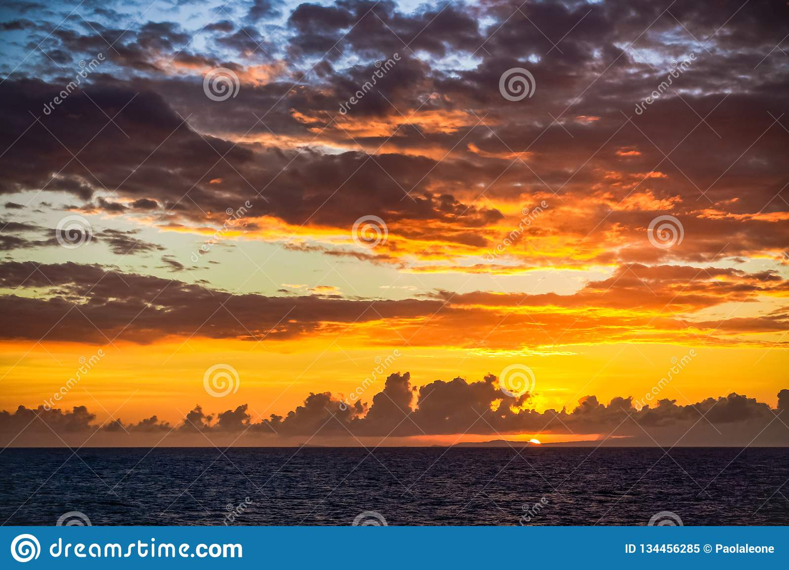 Scenic Sunset on Caribbean Sea with Dark Clouds against an Orange and Blu  Sky. Beautiful Background.