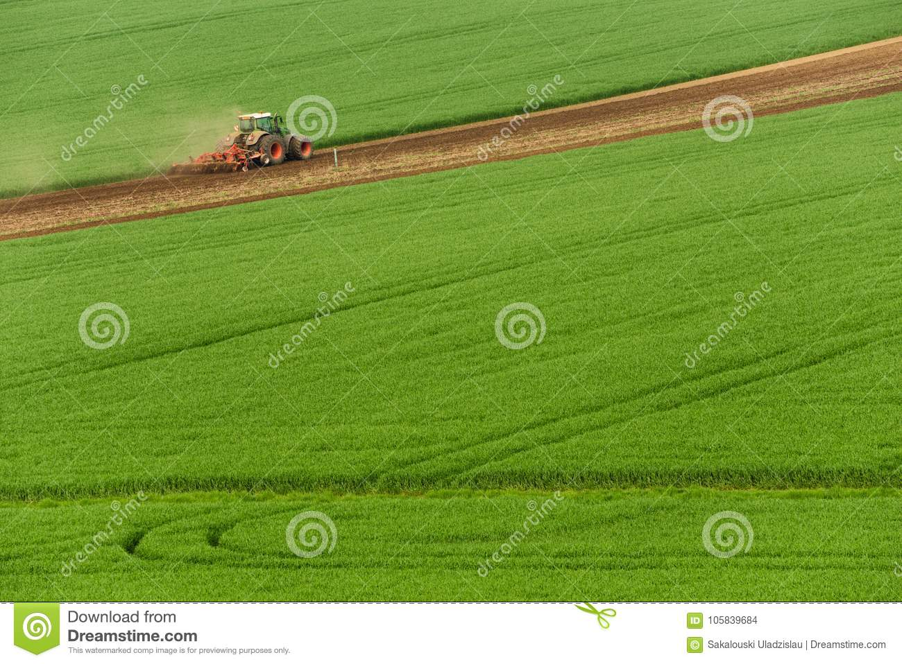 Scenic View Of Modern Farming Tractor Which Plowing Green Field. Agriculture Tractor Cultivating Wheat Field And Creating Green Ab