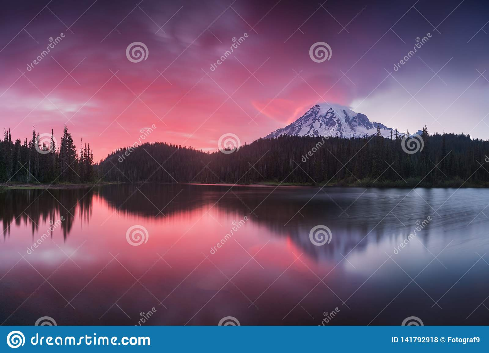 Scenic view of Mount Rainier reflected across the reflection lakes.. Pink sunset light on Mount Rainier in the Cascade Range.