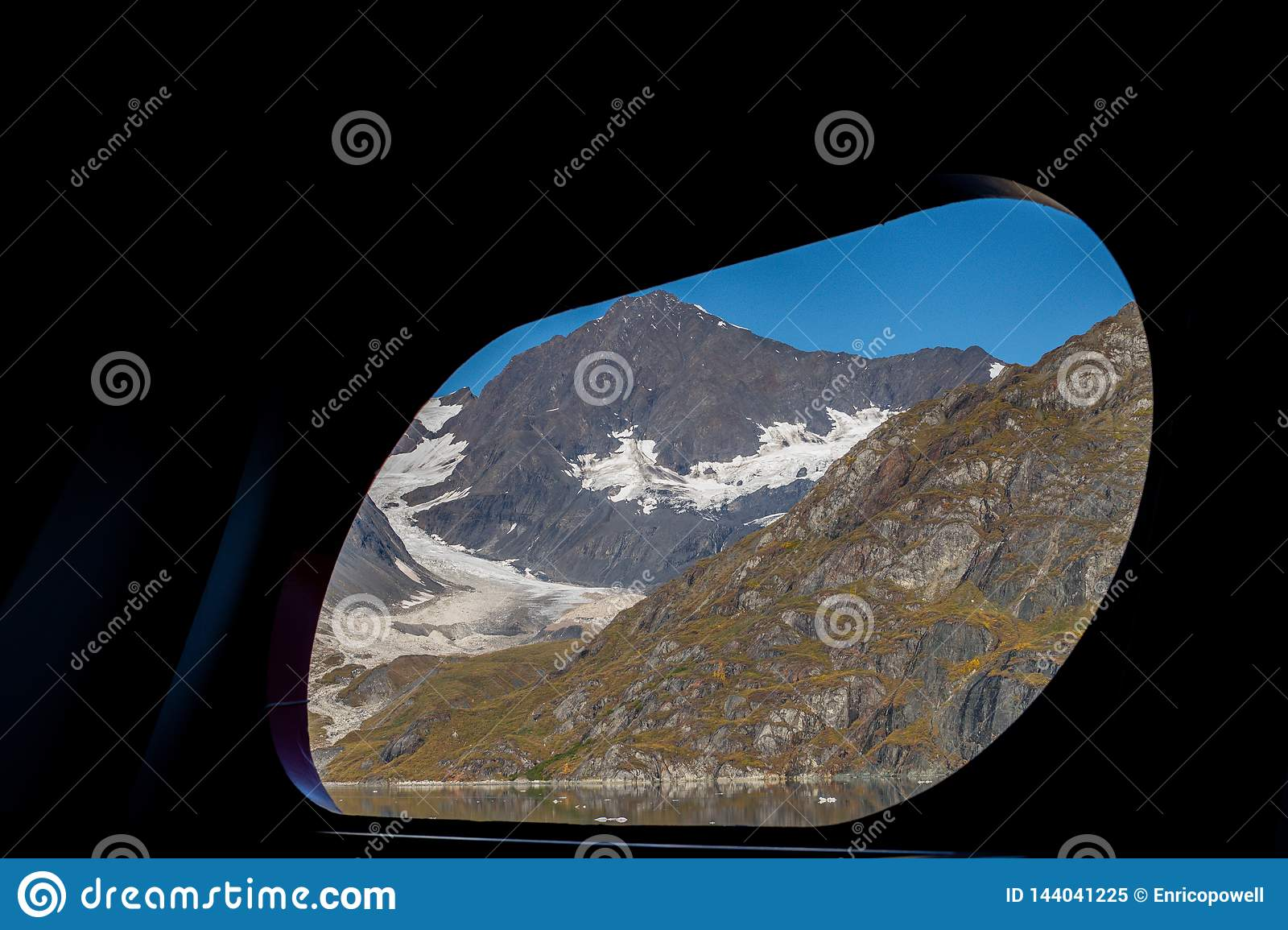 Scenic view through ship port hole/window of snow covered mountains