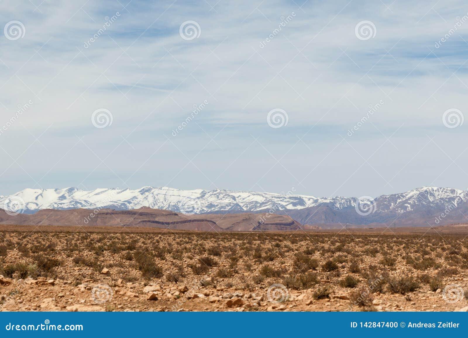 Sceniczny krajobraz wzdłuż poprzedniej karawanowej trasy między Marrakech w Maroko z śniegiem i Sahara zakrywał atlanta pasmo gór