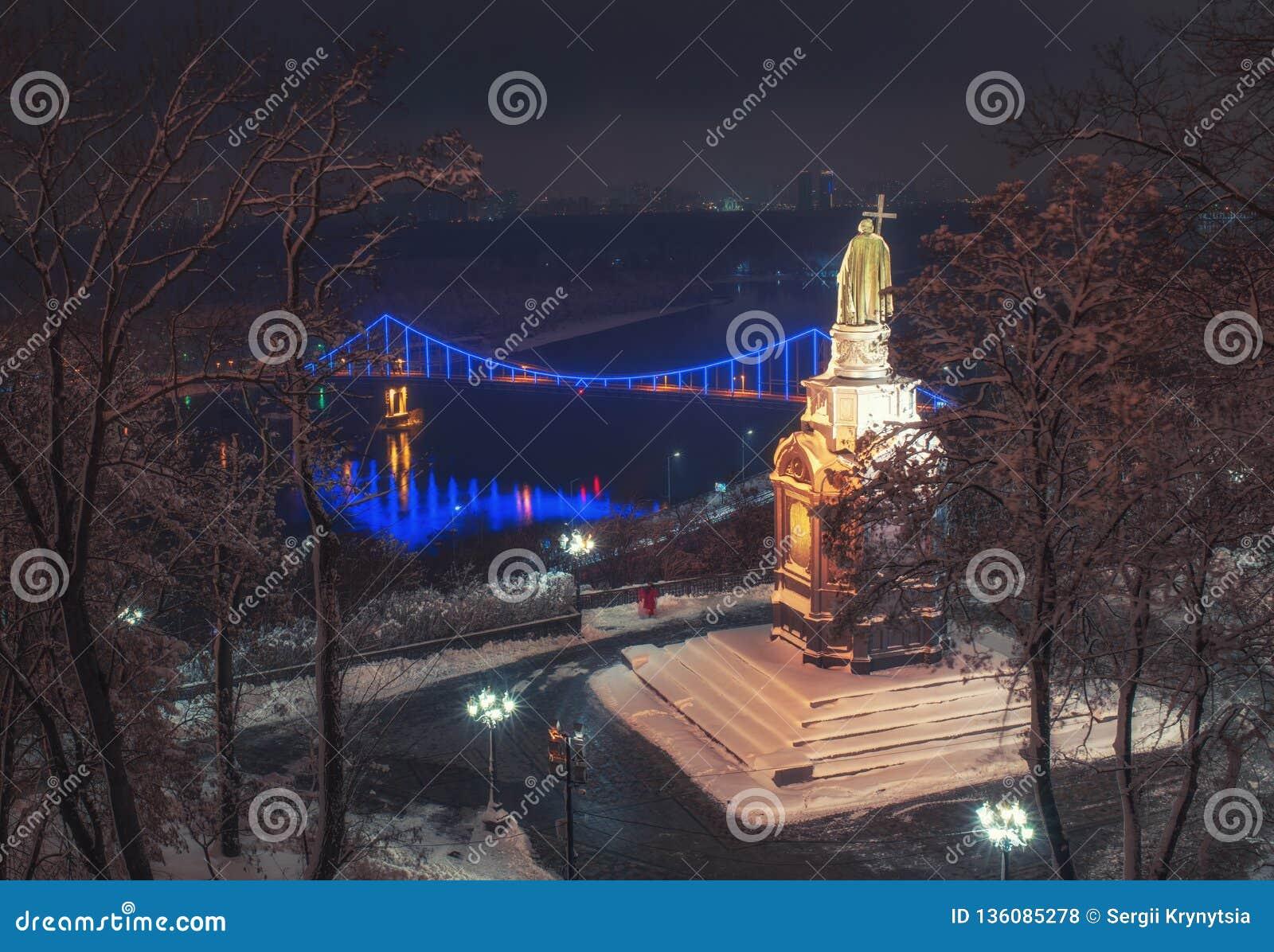 Sceniczny widok Świątobliwy Vladimir zabytek przeciw tłu Zaporoska rzeka przy zimy nocą, Kyiv, Ukraina