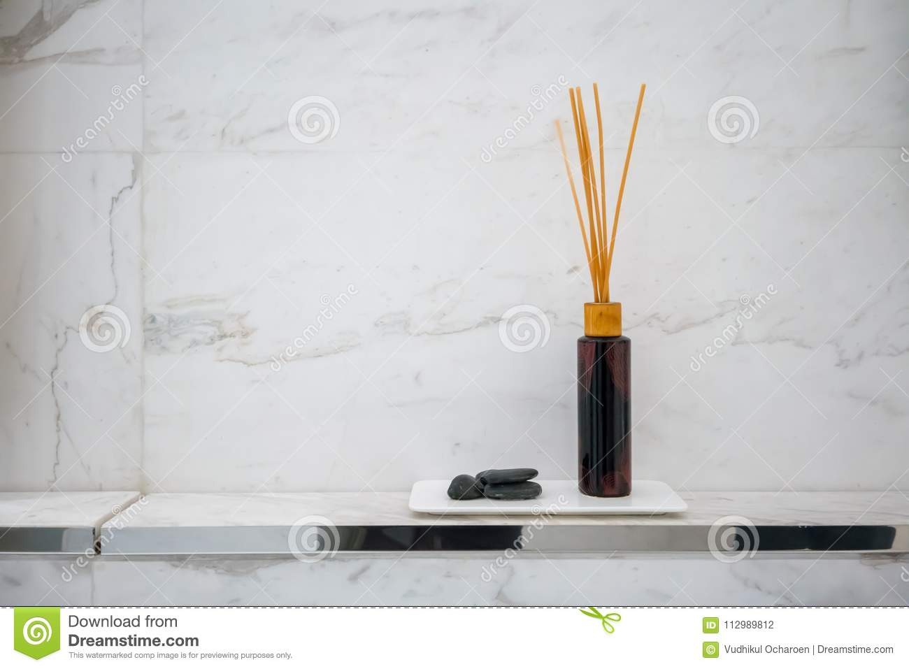 Scented diffuser stick in black glass bottle against white marble wall background