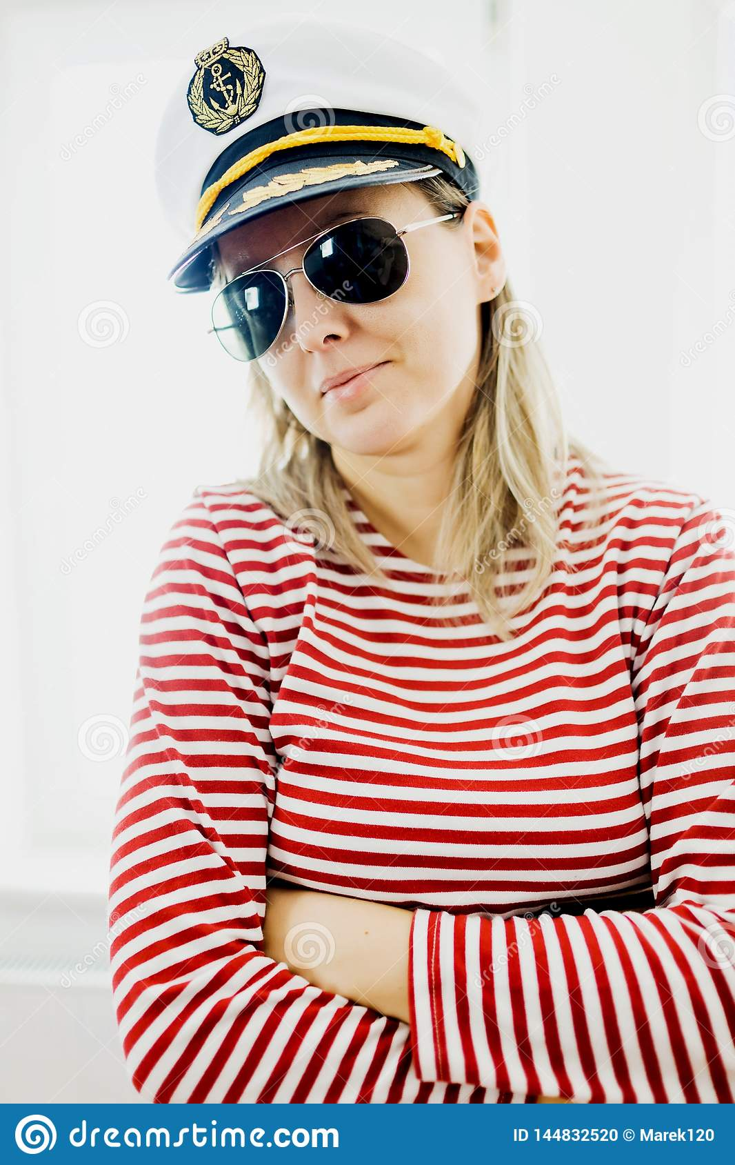 Sceptically young woman sailor in captain cap - wearing red gaps dress