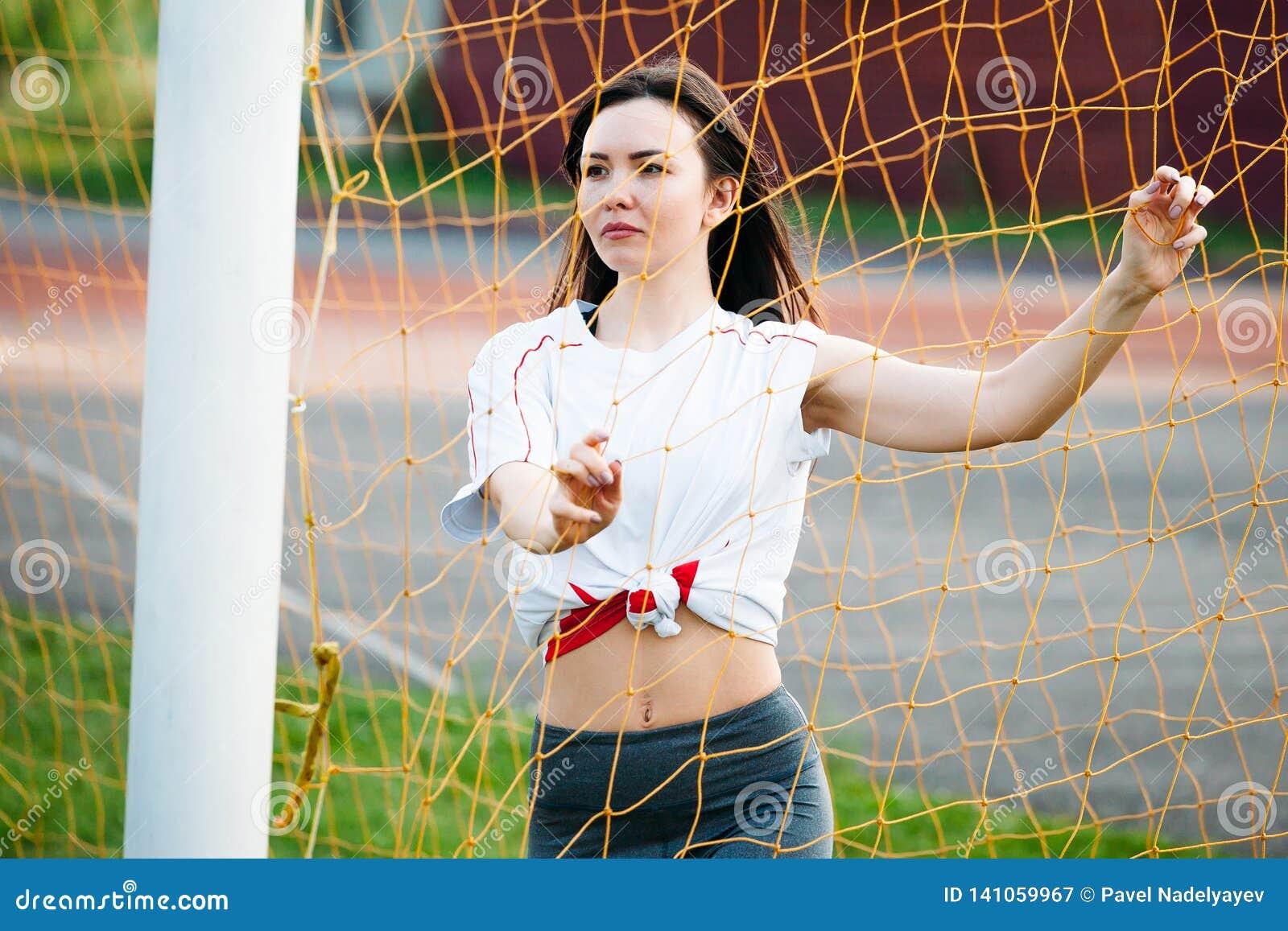 Schöne junge athletische Frau in der Sportkleidung bildet im Stadion auf Hintergrund eines Fußballziels aus mit Fußball Sie ist g