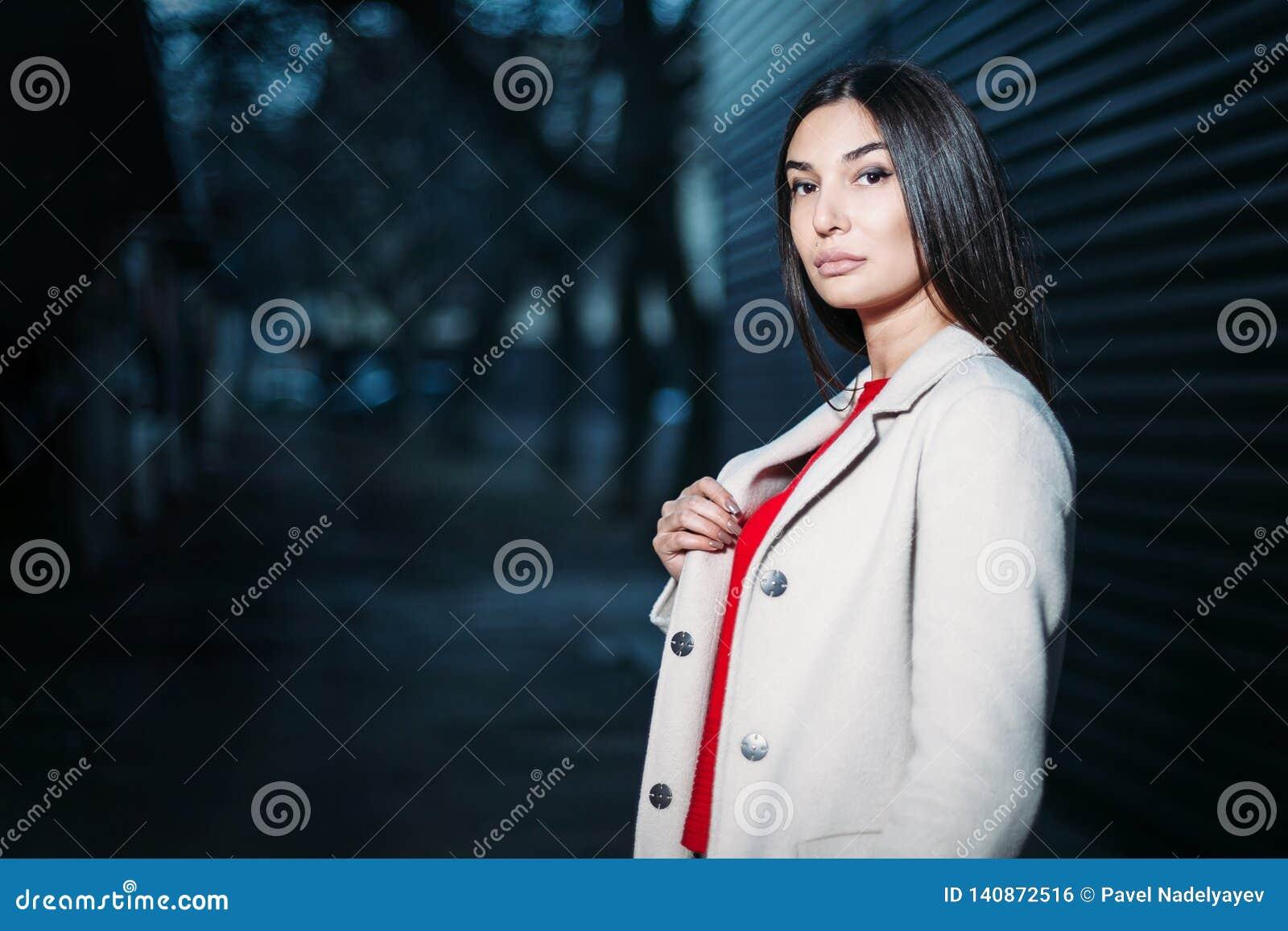 Schöne junge brunette Frau im weißen Mantel der roten Bluse, der draußen glättet Kopieren Sie Platz