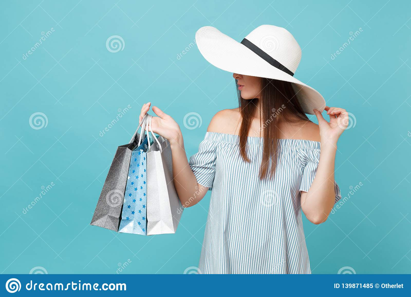 Schöne kaukasische Frau der modernen eleganten Mode des Porträts im Sommerkleid, weiße große breite Randsonnen-Hutholding