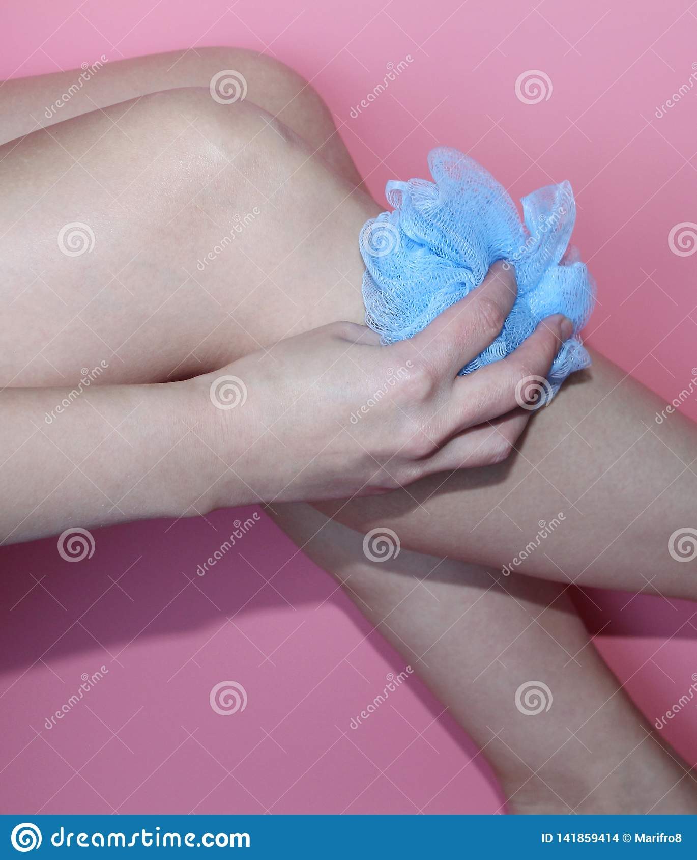 Schöne weibliche Hand, die einen blauen Waschlappen hält Rosa Hintergrund
