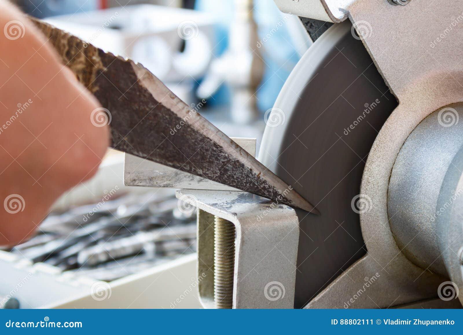 schärfen des messers eines schusters auf schleifmaschinen stockbild
