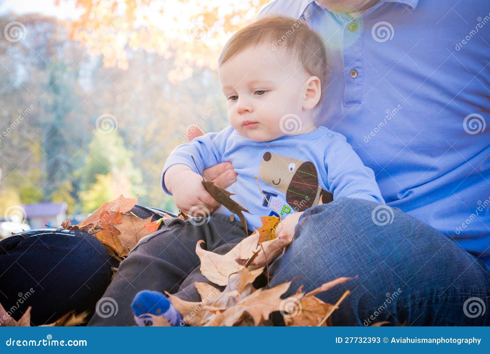 Schätzchen, das in den Blättern spielt