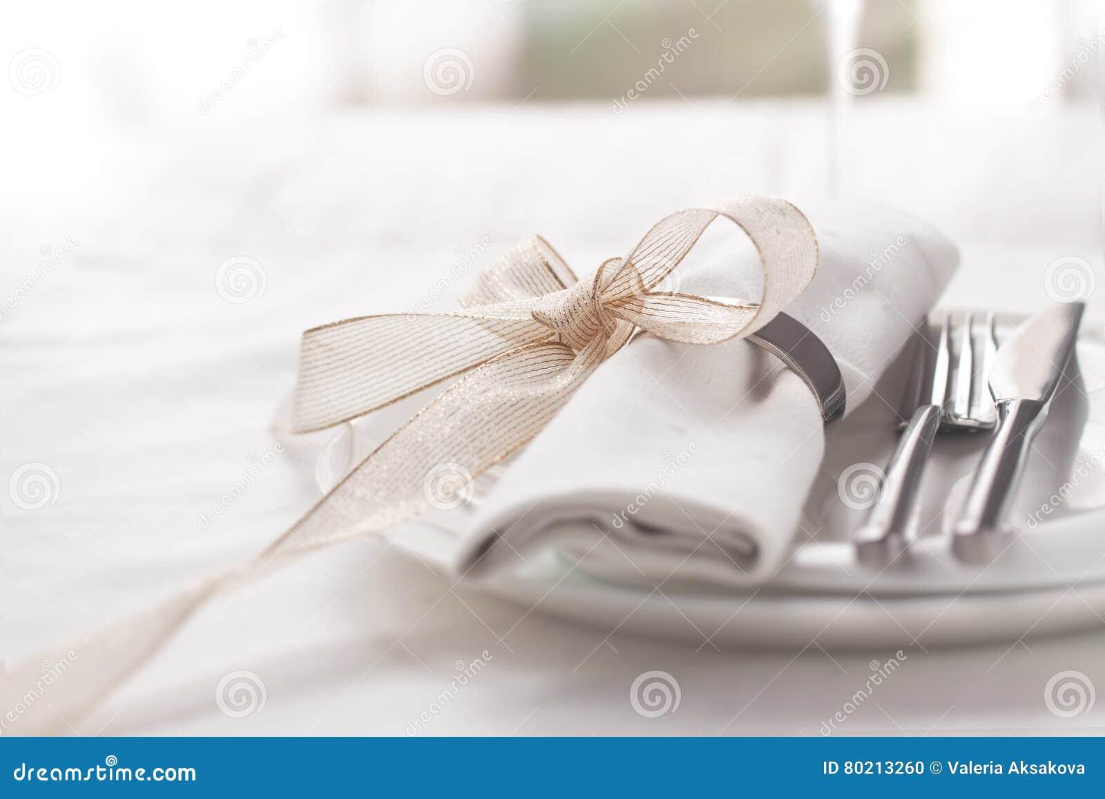 Schön elegante verzierte Tabelle für Feiertag - Hochzeit oder Valentinstag mit modernem Tischbesteck, Bogen, Glas, Kerze und Gesc