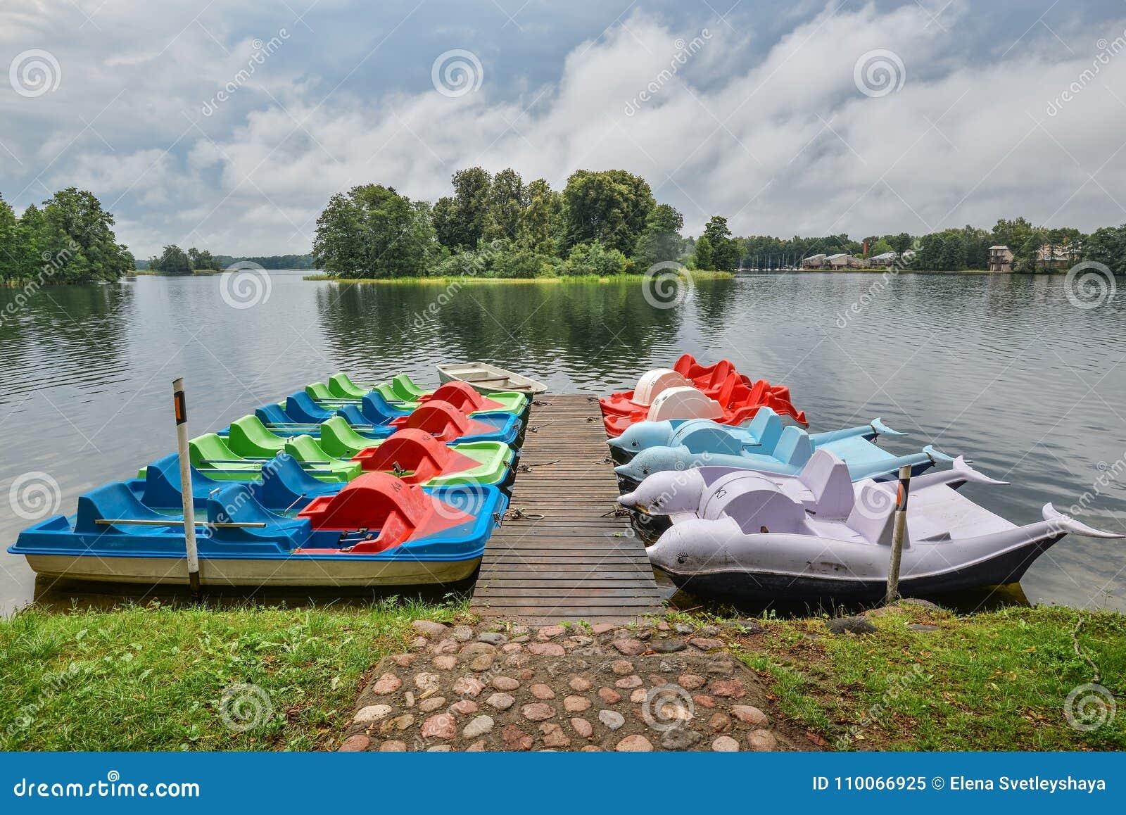 Schöne Abendsommerlandschaft von Trakai See und touristische Boote nähern sich hölzernem Pier See und stürmischer Himmel, Trakai,
